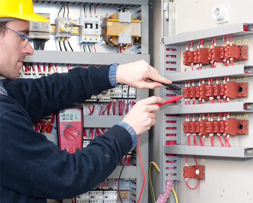 Electrician working inside electrical breaker panel